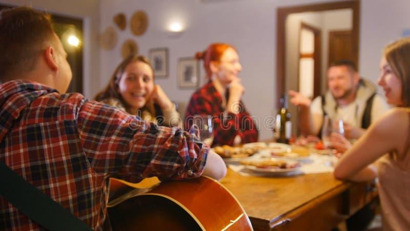 Друзья имея партию - выпивающ и поя песни гитарой стоковое фото rf