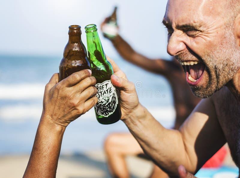 Друзья имея питье на пляже стоковые изображения