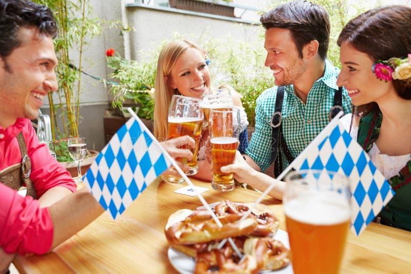Друзья имея потеху в саде пива стоковые фото