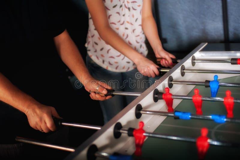 Друзья имея потеху играя foosball таблицы стоковая фотография