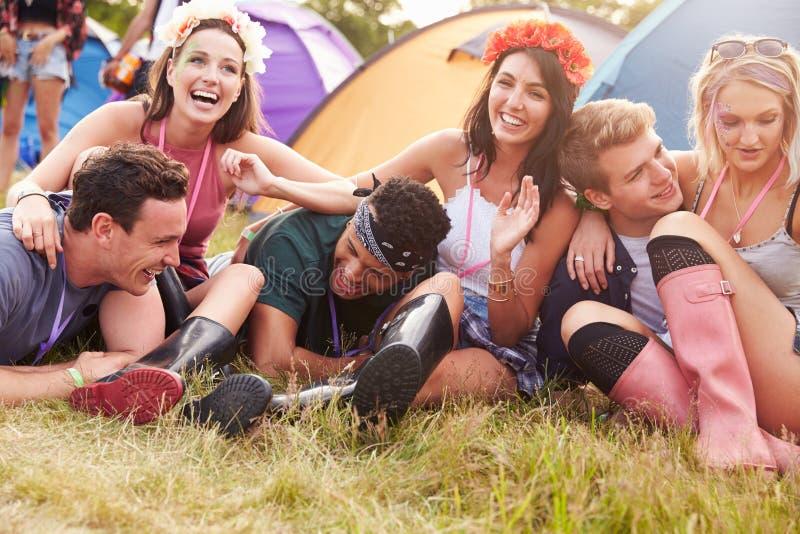Друзья имея потеху на месте для лагеря на музыкальном фестивале стоковое изображение rf