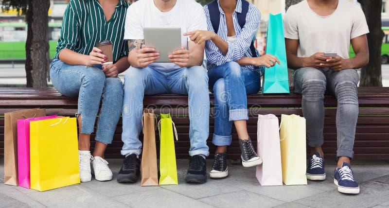 Друзья используя устройства пока сидящ на стенде стоковая фотография