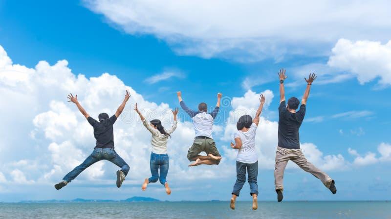 Друзья и сыгранность скача на пляж во время времени захода солнца для дела успеха стоковая фотография rf