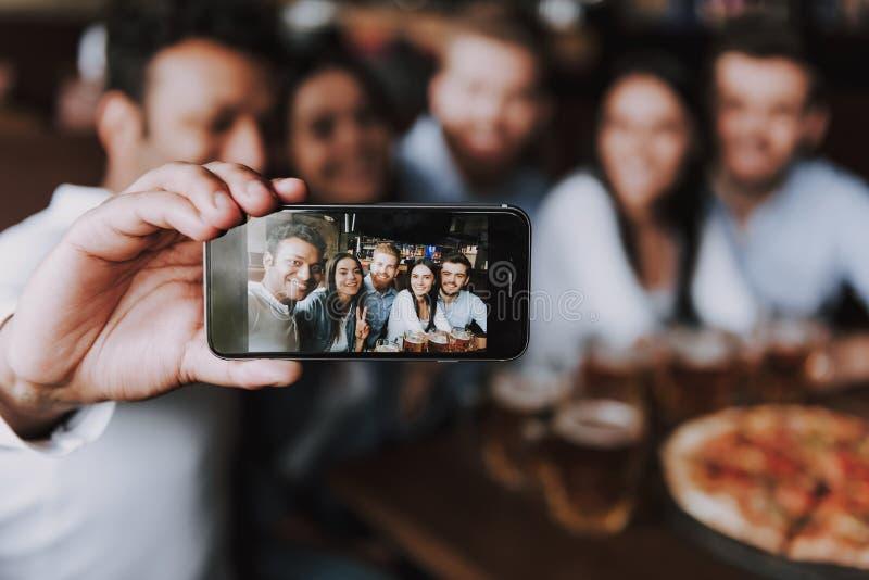 Друзья компании усмехаясь делая Selfie в пабе стоковое фото rf