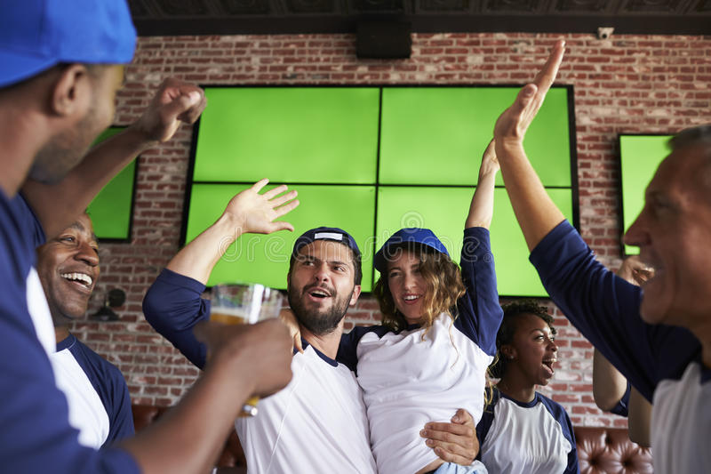 Друзья наблюдая игру в баре спорт на экранах празднуя стоковое изображение rf