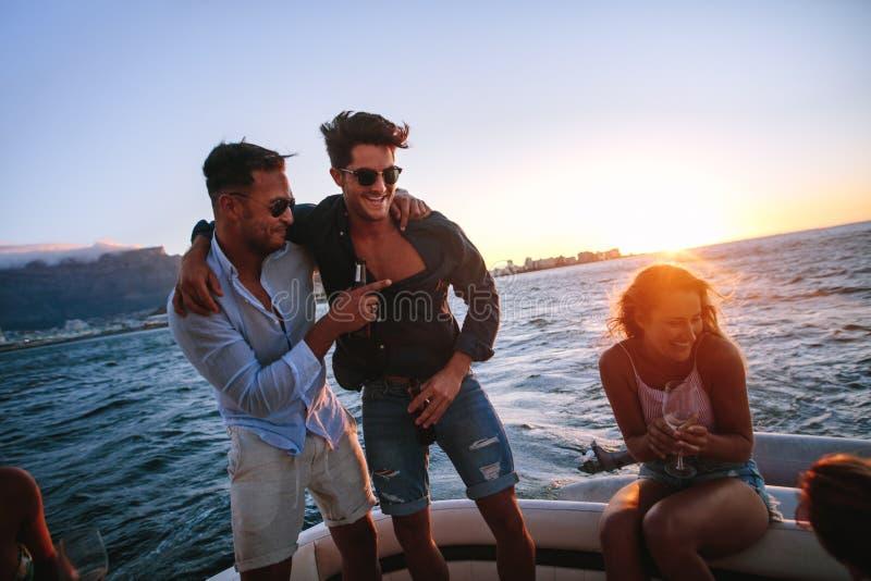 Друзья наслаждаясь в партии шлюпки захода солнца стоковые фото