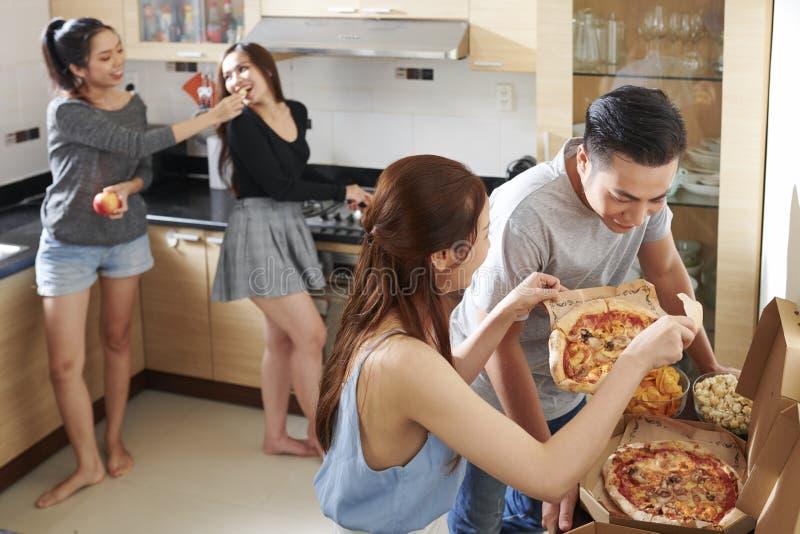 Друзья наслаждаясь домашней партией стоковые фотографии rf