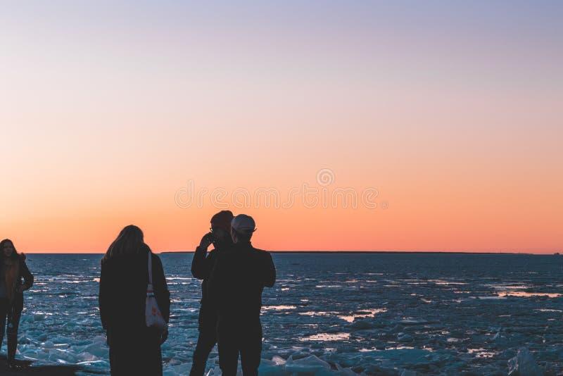 Друзья наслаждаясь заходом солнца морем стоковая фотография rf