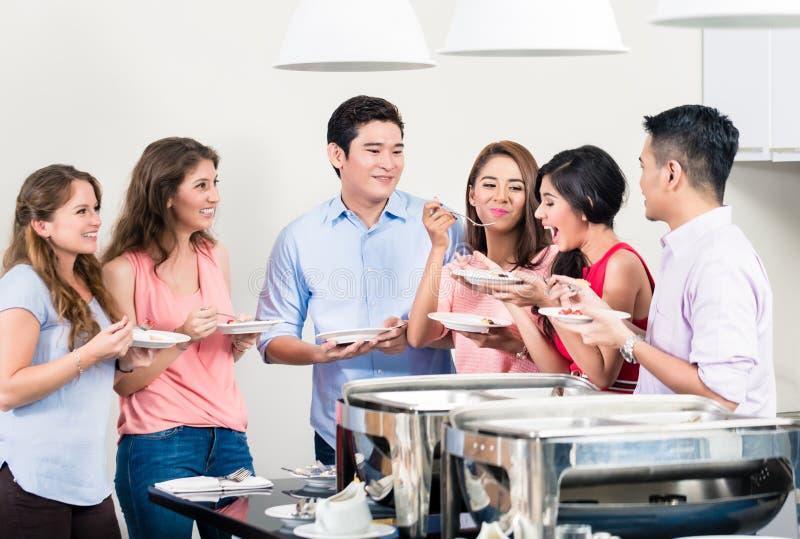 Друзья наслаждаясь обедающим на партии стоковая фотография