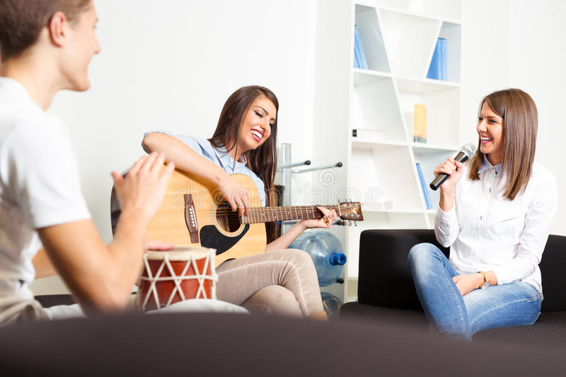 Друзья наслаждаясь играющ гитару и поющ совместно стоковое изображение rf