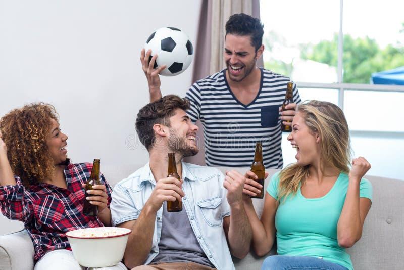 Друзья наслаждаясь пивом пока наблюдающ футбольный матч стоковые изображения