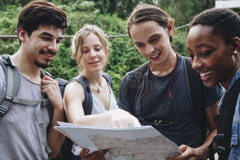 Друзья находя их путь в природе с картой стоковые изображения rf