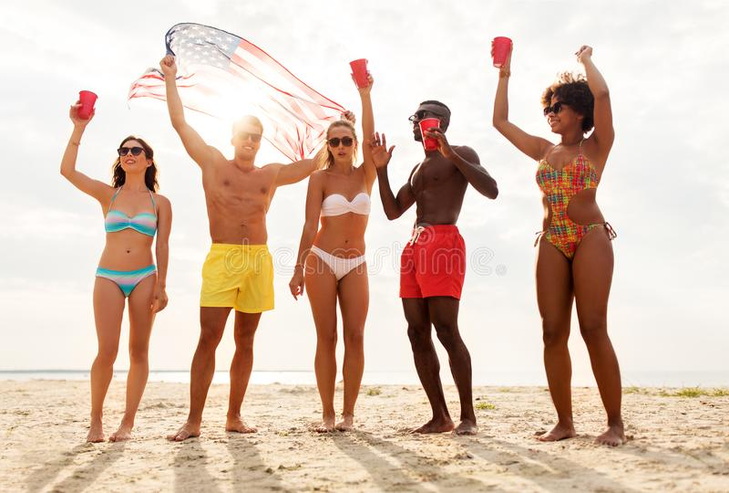 Друзья на американской партии пляжа Дня независимости стоковые изображения