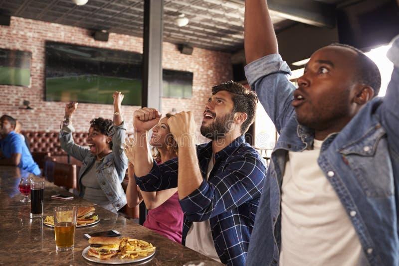 Друзья на счетчике в игре вахты бара спорт и празднуют стоковые изображения rf