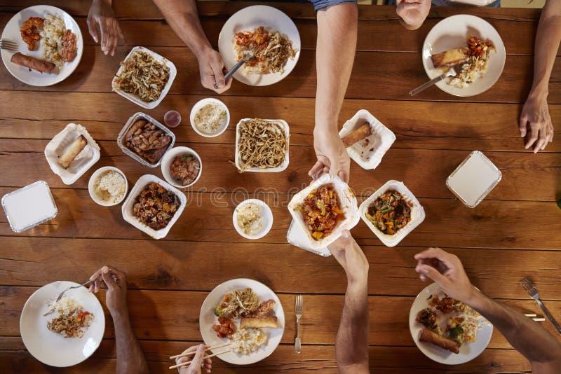 Друзья на таблице деля китайский на вынос, надземный взгляд стоковая фотография rf