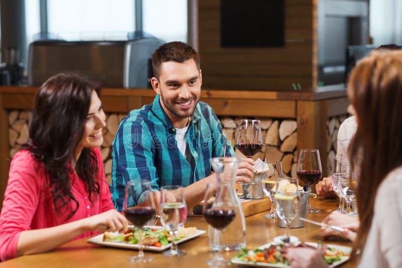 Друзья обедая и выпивая вино на ресторане стоковые изображения rf
