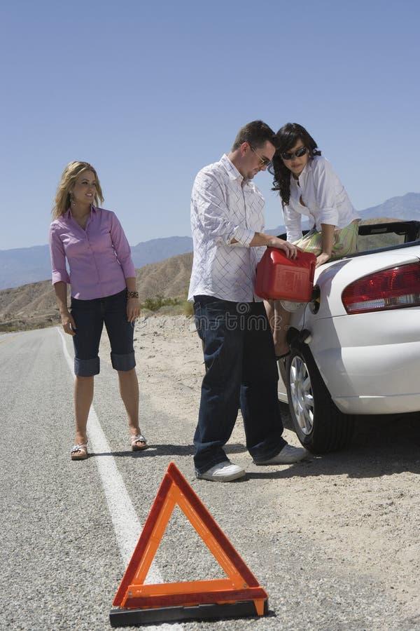 Друзья дозаправляя автомобиль с предупреждающим треугольником на переднем плане стоковое изображение rf