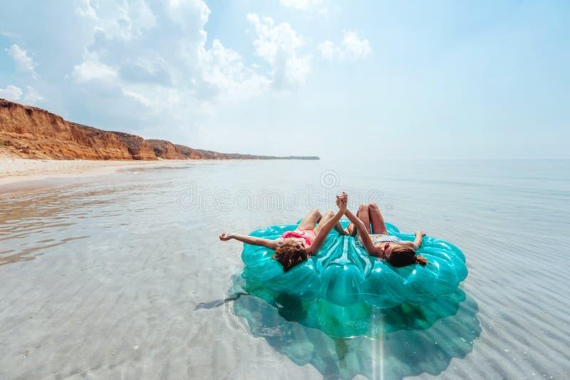 Друзья ослабляя на раздувном кольце на пляже стоковое фото rf