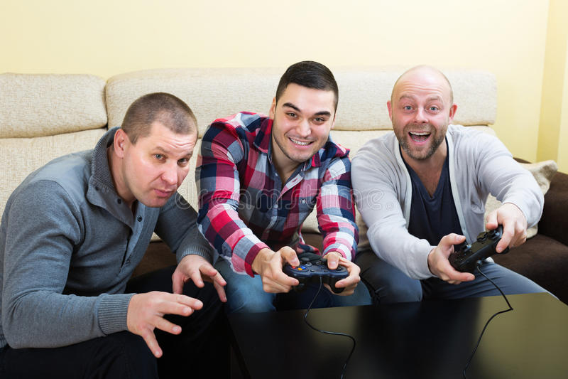 Друзья ослабляя с видеоигрой стоковая фотография