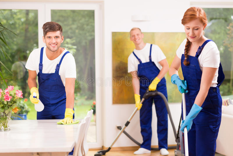 Друзья очищая квартиру стоковые изображения rf