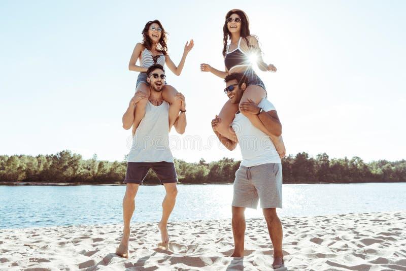 Друзья перевозить и наслаждаясь летнее время пока тратящ время на пляже стоковое изображение