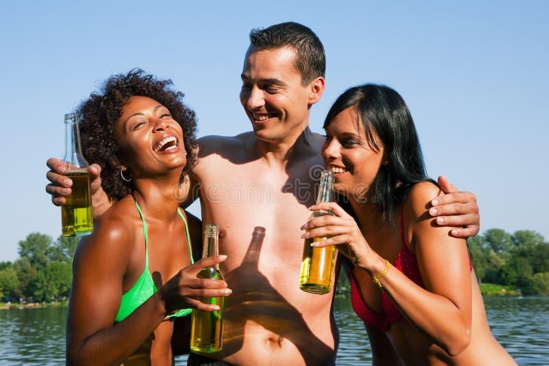 друзья пива выпивая собирают swimwear стоковое фото