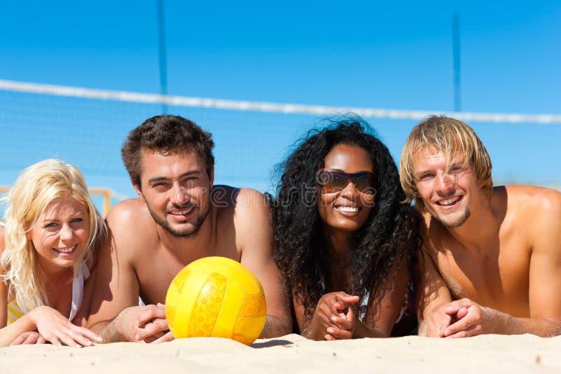друзья пляжа играя волейбол стоковая фотография