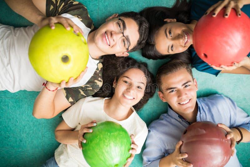Друзья показывая красочные шарики боулинга пока лежащ на переулке стоковые фотографии rf