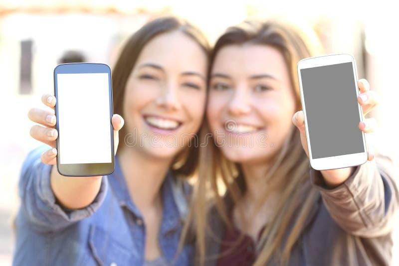 Друзья показывая 2 умных экрана телефона