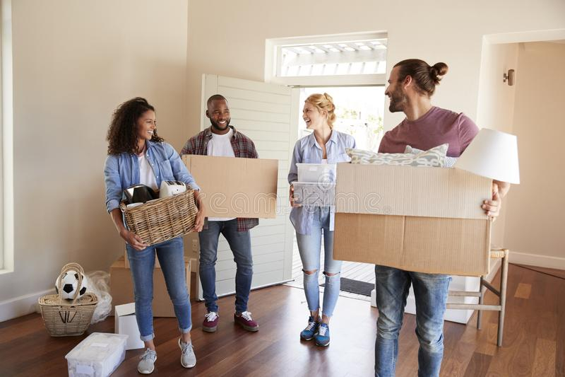 Друзья помогают парам для того чтобы снести коробки в новый дом на Moving день стоковые фото