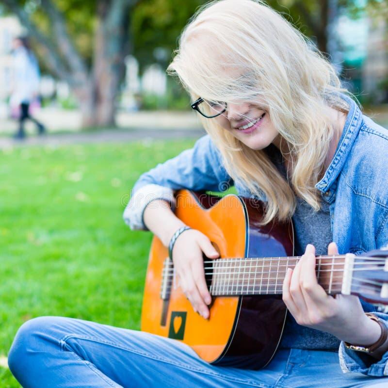 Друзья поя песни в парке имея потеху стоковые фото