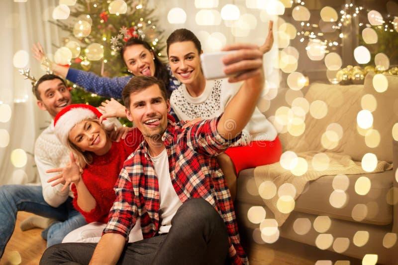 Друзья празднуют Рождество и принимают селфи стоковые фото