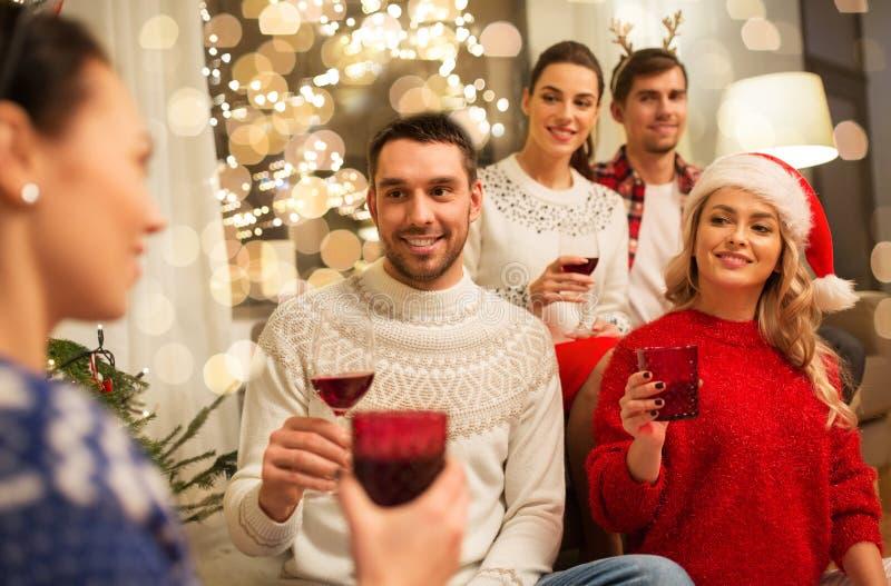 Друзья празднуют Рождество и пьют вино стоковое изображение rf