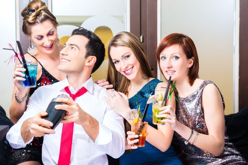 Друзья празднуя с barkeeper в коктейль-баре стоковые фото