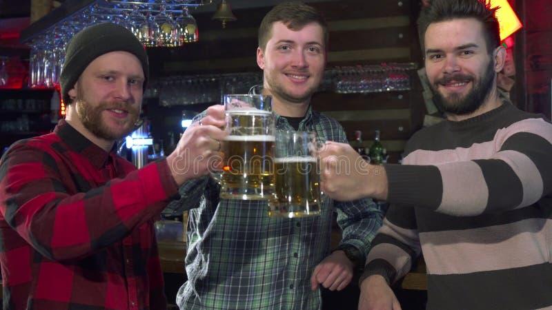 Друзья представляют с стеклами пива на пабе стоковые изображения rf