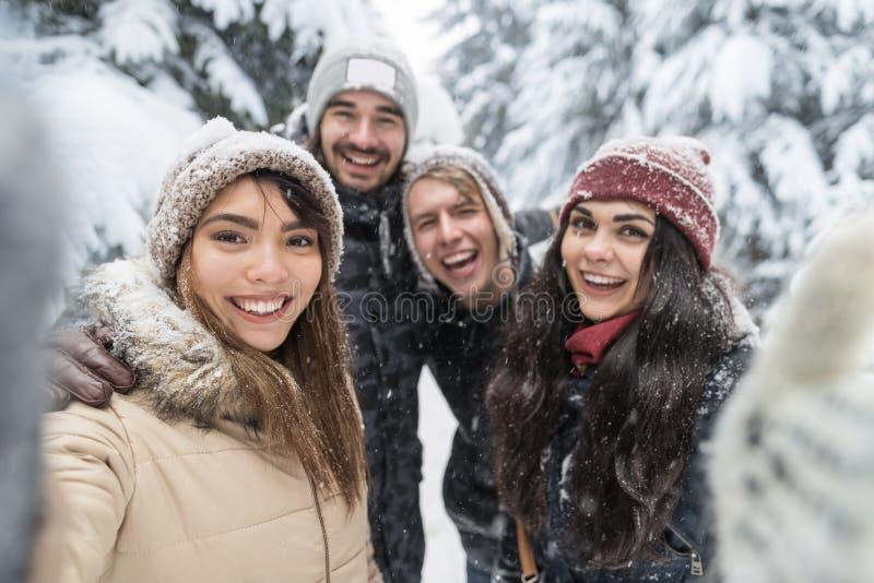 Друзья принимая молодые люди леса снега улыбки фото Selfie группу внешнюю стоковые изображения rf