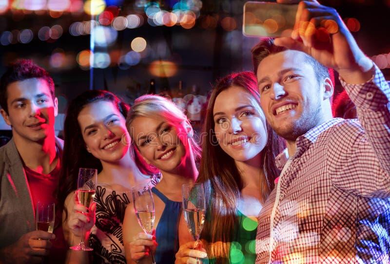 Друзья принимая selfie smartphone в ночном клубе стоковая фотография