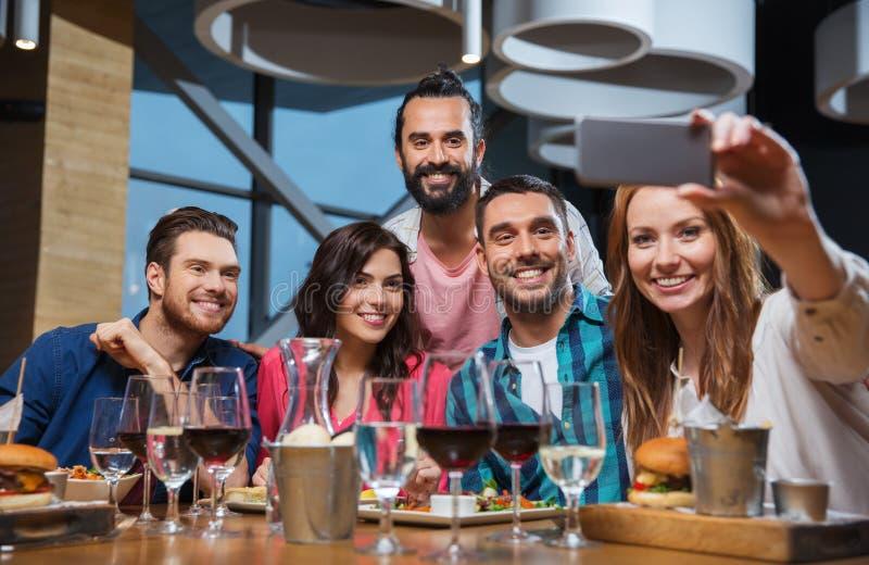 Друзья принимая selfie smartphone на ресторане стоковое фото rf