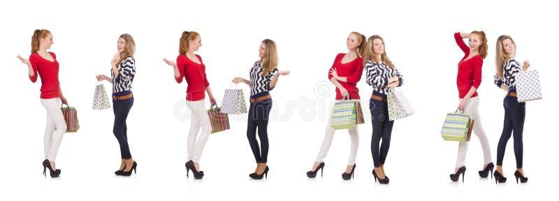 Друзья при хозяйственные сумки изолированные на белизне стоковые фото
