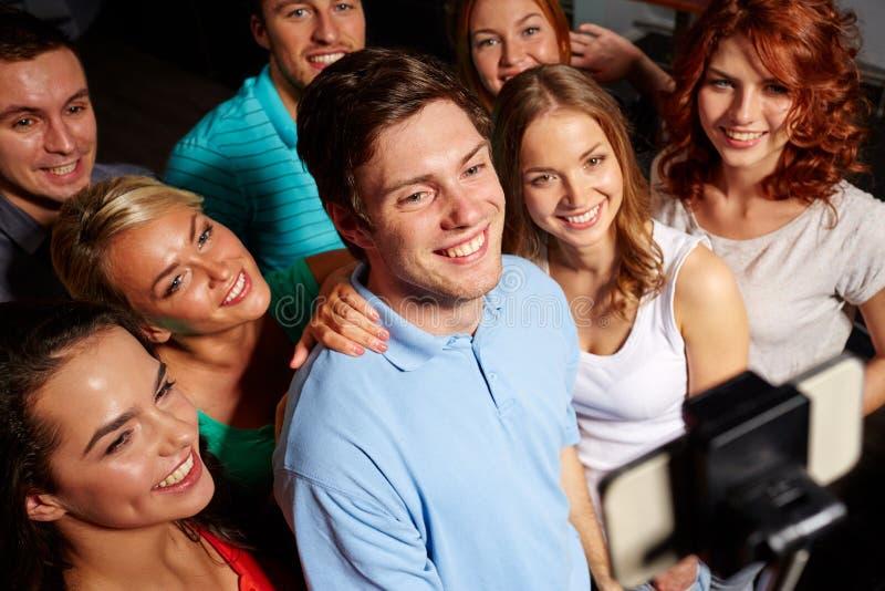 Друзья при smartphone принимая selfie в клубе стоковые фото