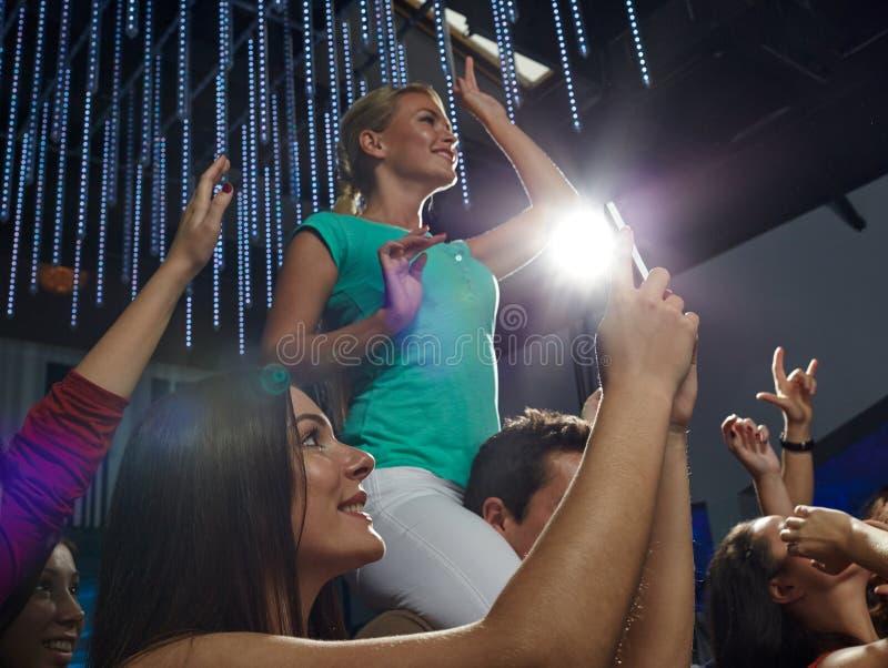 Друзья при smartphone фотографируя на концерте стоковые изображения