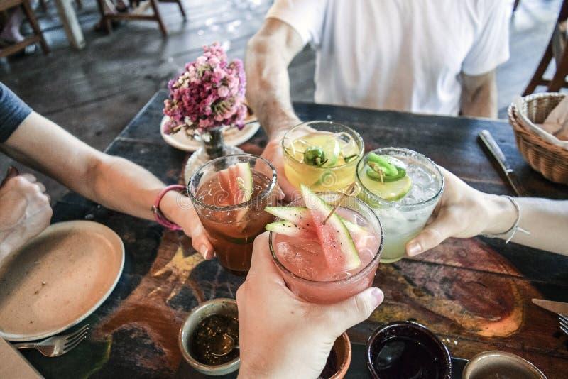 Друзья провозглашать с тропическими пить стоковое фото