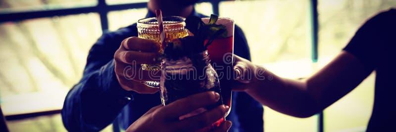 Друзья провозглашая тост стекла напитков в баре стоковые фото