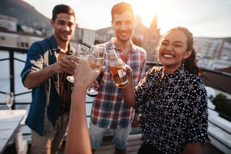 Друзья провозглашать пить на крыше стоковая фотография rf