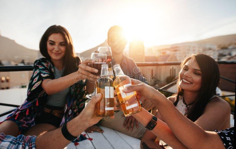 Друзья провозглашать пить на партии крыши стоковые изображения rf