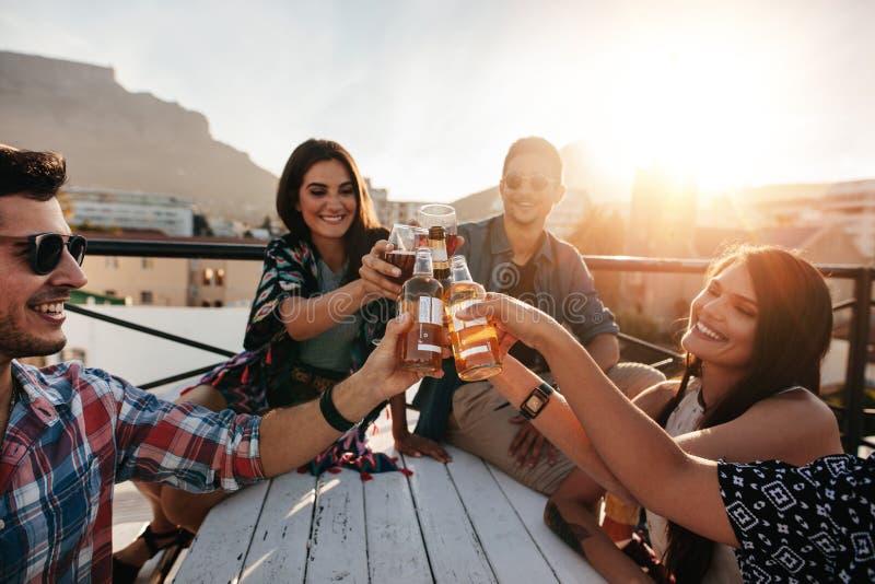 Друзья провозглашать пить на партии крыши стоковое изображение rf
