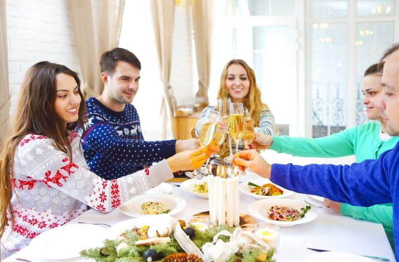 Друзья провозглашать с шампанским пока имеющ рождественский ужин стоковая фотография