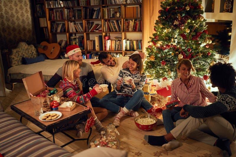 Друзья сидят рядом с рождественской елкой, едят рождественские печенье, пьют какао и веселятся стоковые изображения rf
