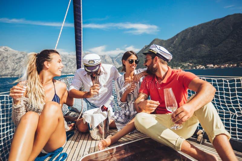 Друзья сидя на палубе парусника и имея потеху Каникулы, перемещение, море, приятельство и концепция людей стоковая фотография rf