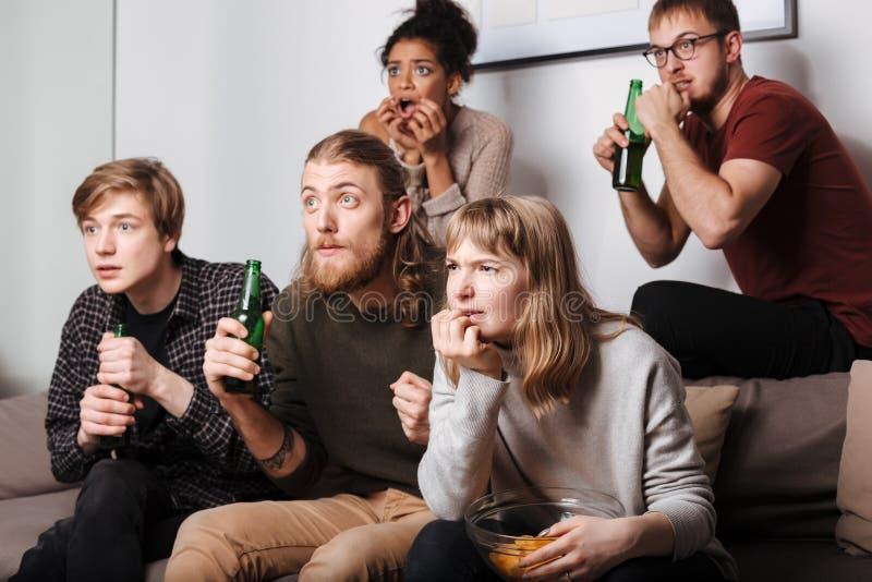 Друзья сидя на софе и умышленно смотря фильм вместе с хрустящими корочками и пивом дома стоковое фото rf